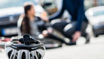 closeup of bike helmet with bike, biker and person trying to help on the background Dan Rose Law Firm