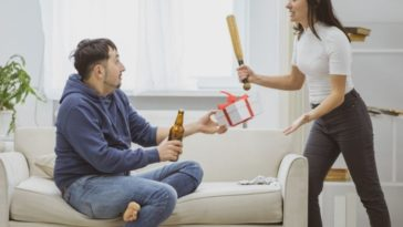 A husband is drinking beer while her wife beats him with a bat