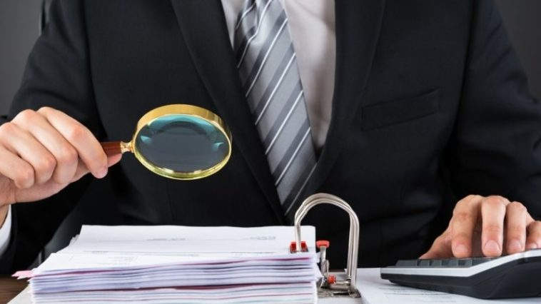 Businessman Inspecting Invoice With Magnifying Glass At Wooden Desk